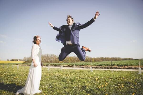 Mari s'amuse pendant les photos À sauter en l'air moments forts de votre mariage en photos