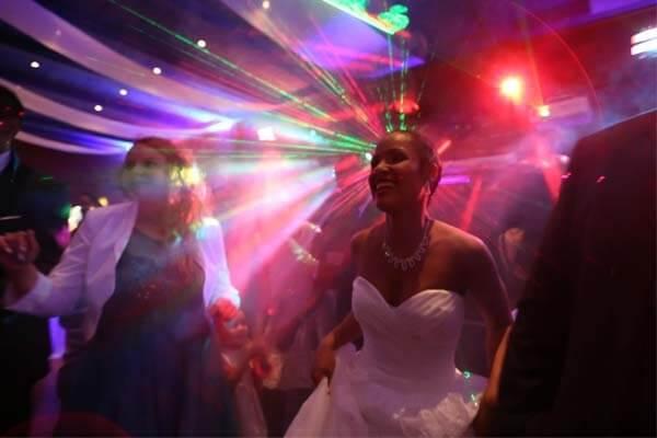 La mariée qui s'amuse à la soirée et qui danse sur le dance Floor dans la lumière